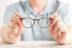 Optometrist giving new glasses. On table Royalty Free Stock Photos