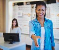 Optometrist greeting a customer at the door. Pretty young African American optometrist greeting a customer at the door with a beaming smile and outstretched hand stock photos