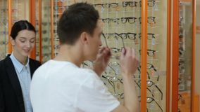 Optometrist helping client to choose eyeglasses stock footage