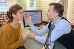 Optometrist helping pretty client to purchase eyeglasses Stock Photography