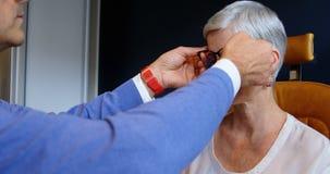 Optometrist het aanpassen oogglazen op geduldige ogen 4k stock videobeelden