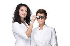 Optometrist holding an eye test glasses and giving Royalty Free Stock Photography