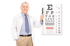 Optometrist holding glasses in front of eye chart Royalty Free Stock Photo