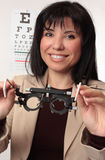 Optometrist holding trial frames. Friendly smiling optometrist holding a pair of trial frames Royalty Free Stock Image