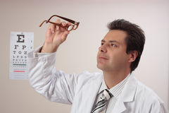 Optometrist inspects eye glasses Stock Photos