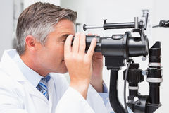 Optometrist looking in optical instrument Stock Photos