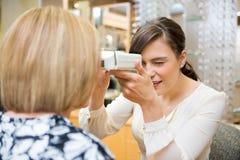 Optometrist Measuring Pupilary Distance. Female optometrist measuring pupilary distance on female customer Royalty Free Stock Image