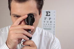 Optometrist or ophthalmic surgeon. An optometrist turning the lens dial of the opthalmoscope while examining a patient's eyes Stock Photos