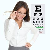Optometrist / optician. Optician or optometrist showing Snellen eye exam chart wearing eye wear glasses. Female mixed race Caucasian / Asian Chinese model Royalty Free Stock Images