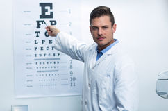 Optometrist pointing at eye chart Stock Images