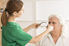 Optometrist prescribing spectacles to elderly man. Female optometrist prescribing spectacles to elderly men patient in ophthalmology clinic Royalty Free Stock Image