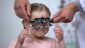 Optometrist putting special glasses on little girl, diagnosing Lazy eye illness