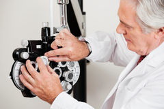 Optometrist Setting Phoropter For Eye Test Stock Photos