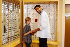 Optometrist showing glasses to young lad Royalty Free Stock Images