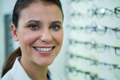 Optometrist in spectacles smiling in optical store Stock Photography