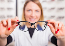 Optometrist suggesting glasses. Optometrist suggesting modern optic glasses royalty free stock photos