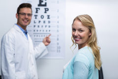 Optometrist taking eye test of female patient Stock Image