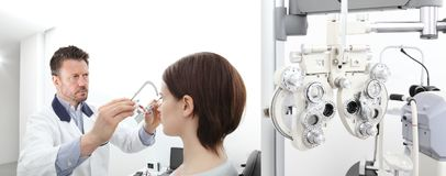 Optometrist with trial frame examining eyesight woman patient i. Optometrist with trial frame examining eyesight women patient in optician office stock photo