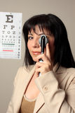 Optometrist vision checkup. Optometrist using an opthalmoscope to check eyes Stock Photo