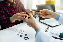 Optometrist visit - woman get her new glasses at optician office. Optometrist visit - woman get her new optical glasses at optician office stock images