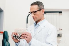 Optometrist in white coat looking at trial frame in hands. In clinic royalty free stock photos