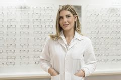 Optometrist woman looking glassea at display in optical store wi Royalty Free Stock Photography