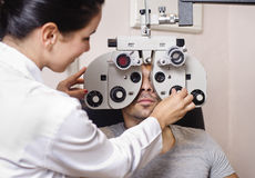 Optometrist woman looking phoropter calibration. Optometrist women looking phoropter calibration in young brunette man Royalty Free Stock Image