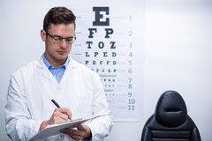 Optometrist writing on clipboard. Attentive optometrist writing on clipboard in ophthalmology clinic Stock Images