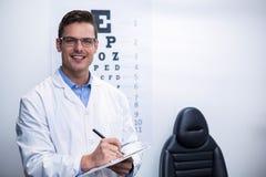 Optometrist writing on clipboard. Portrait of optometrist writing on clipboard in ophthalmology clinic Stock Photos
