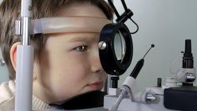 Optometrist wykonuje wizualnego śródpolnego test młoda chłopiec Zdjęcia Royalty Free
