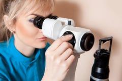 Optometrista adulto joven serio del doctor en el trabajo con el dispositivo f Fotos de archivo libres de regalías