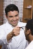 Optometrista Assisting Male Patient en elegir los vidrios Fotografía de archivo libre de regalías