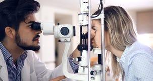 Optometrista atento que examina al paciente femenino en la lámpara rajada fotos de archivo libres de regalías