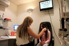 Optometrista che controlla gli occhi delle bambine Immagine Stock