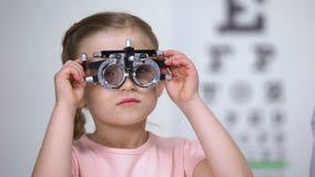 Optometrista che mette phoropter sulla bambina, bambino che protesta per non vedere niente video d archivio