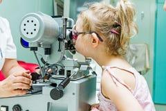 Optometrista con il paziente, dante un esame degli occhi immagini stock libere da diritti