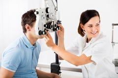 Optometrista de sexo femenino Doing Sight Testing para el paciente Imágenes de archivo libres de regalías