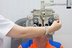 Optometrista de sexo femenino Doing Sight Testing para el paciente masculino en clínica Fotografía de archivo libre de regalías
