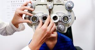 Optometrista de sexo femenino que examina al paciente joven en chiropter almacen de metraje de vídeo