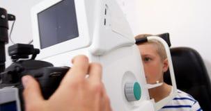 Optometrista de sexo femenino que examina al paciente joven en coreometry almacen de video