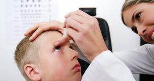 Optometrista de sexo femenino que pone descenso de ojo en ojos pacientes jovenes almacen de metraje de vídeo