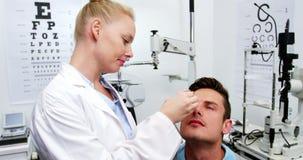 Optometrista de sexo femenino que pone ojos el hospitalizado del descenso de ojo almacen de video