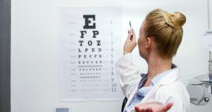 Optometrista de sexo femenino que señala en la carta de ojo metrajes