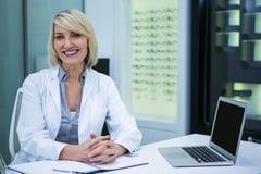 Optometrista de sexo femenino que se sienta en clínica de la oftalmología foto de archivo