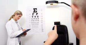 Optometrista de sexo femenino que toma la prueba del ojo del paciente joven almacen de video