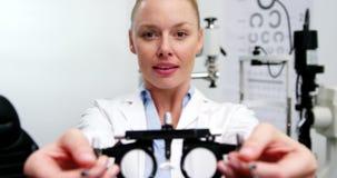 Optometrista de sexo femenino sonriente que lleva a cabo el messbrille metrajes