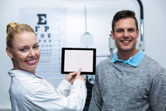 Optometrista fêmea que tem a discussão com o paciente na tabuleta digital foto de stock