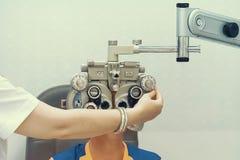 Optometrista femminile Doing Sight Testing per il paziente maschio in clinica immagine stock libera da diritti