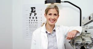 Optometrista hermoso que se coloca en clínica de la oftalmología almacen de video