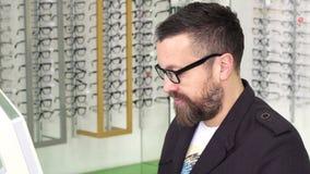 Optometrista profesional que trabaja en un ordenador en su tienda almacen de video